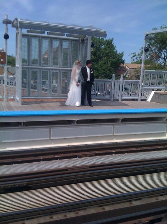 Bride and Groom hold hands, in full wedding garb, and wait on Chicago El platform