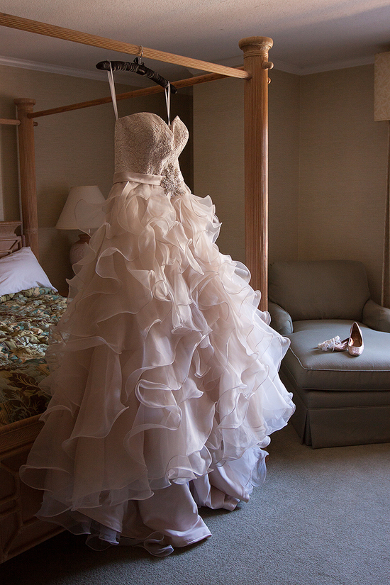 blush pink gown hangs from bed