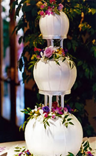 Globe-shaped-three-tier-white-wedding-cake-adorned-with-fuschia-purple-and-yellow-flowers.full