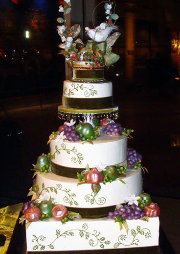 Velvet-earth-regal-4-tier-wedding-cake-white-with-green-leaf-vine-design-purple-grapes-red-plums-green-doves-on-top.full