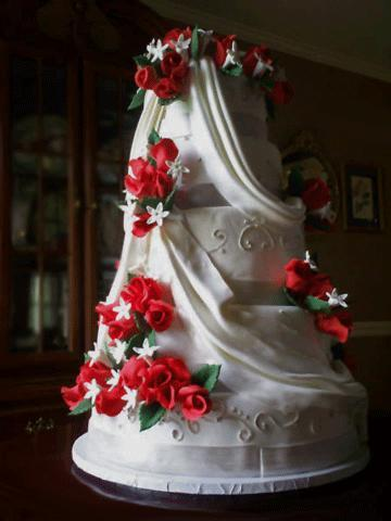 White-classic-wedding-cake-with-bright-red-roses-green-leafs.full