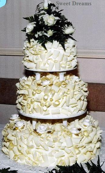 White-dreamy-wedding-cake-white-chocolate-circular-shavings-white-roses.full