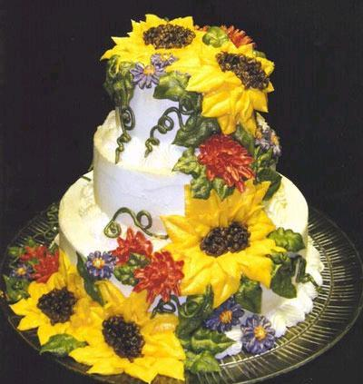 White-wedding-cake-with-large-yellow-sunflowers-green-leafs-red-purple-smaller-flowers.full