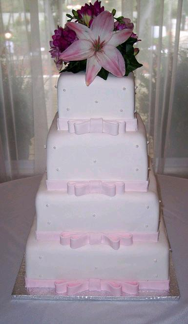 Blushing-pink-white-tiered-wedding-cake-with-pearls-and-light-pink-bows.full
