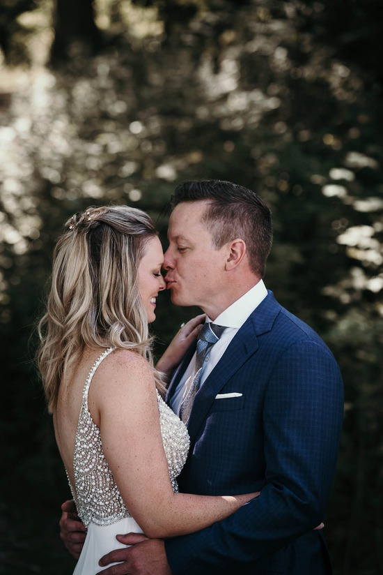 Groom kissing bride's nose during portrait session