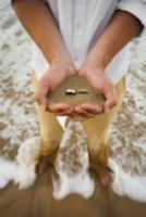 Groom_holding_rings_in_sand.full