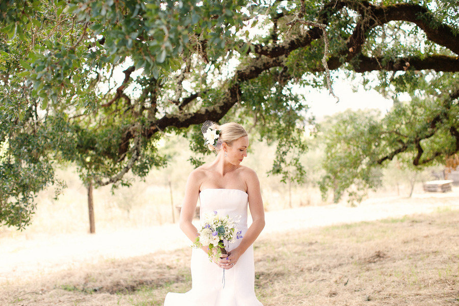 romantic bride poses beneath big tree ranch wedding venue