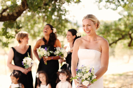 bride smiles with bridesmaids in back
