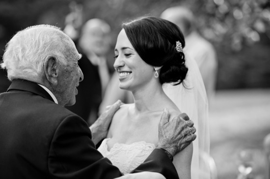 bride smiles while grandpa embraces her before wedding ceremony