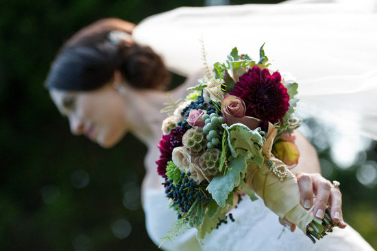 brunette bride shows off rustic bridal bouquet