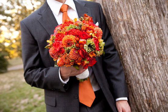 vibrant orange bridal bouquet held by groom