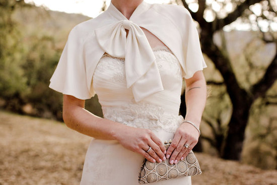 bride wears ivory bridal cape with bow