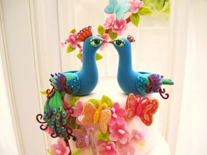 photo of Vibrant peacock wedding cake topper
