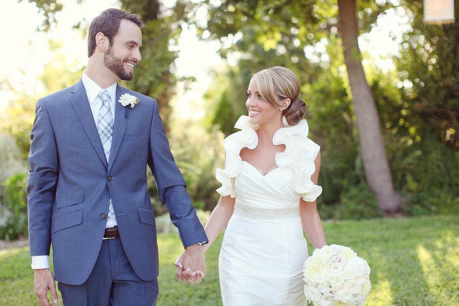 Bride-groom-smile-hold-hands-outside-wedding-venue.full