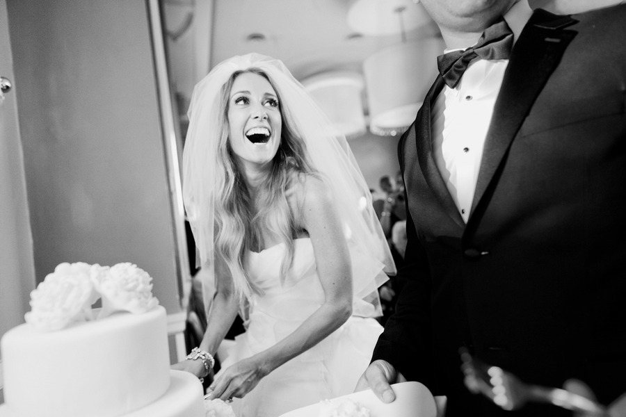 bride looks up at groom while cutting cake