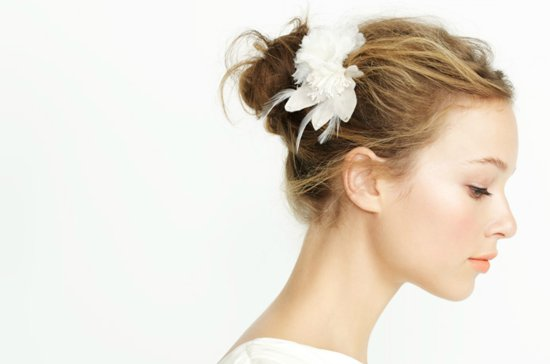 Wispy bridal updo with flower accessories.
