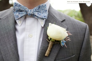 photo of mens wedding attire groom wears blue bow tie floral print grey tailored suit