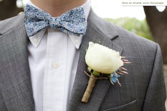 groom wears blue bow tie floral print grey tailored suit