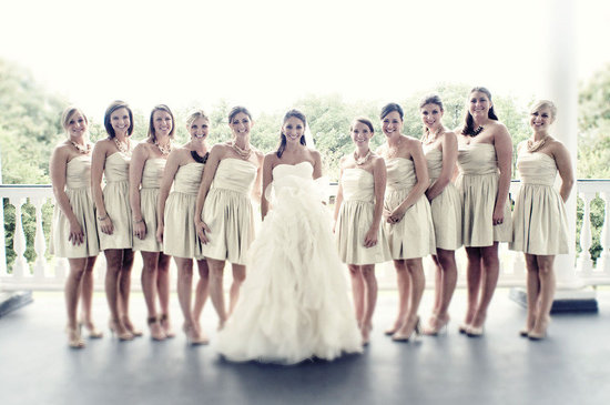 bride poses with bridesmaids in short gold dresses