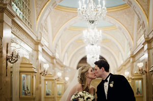 photo of elegant wedding venue bride groom kiss beneath chandeliers