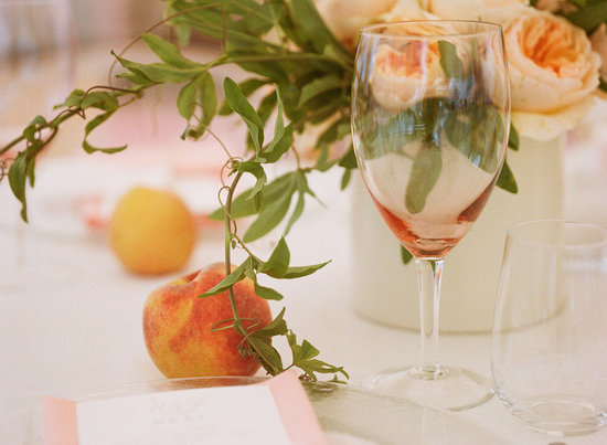 elegant real wedding outdoor reception under tent peaches used for centerpieces