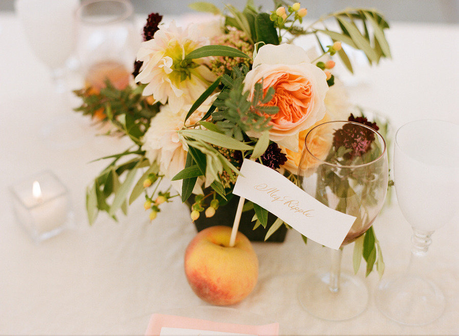 elegant real wedding outdoor reception under tent peach escort card holders
