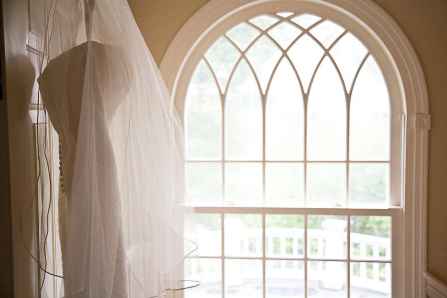 Elegant-real-wedding-outdoor-reception-under-tent-wedding-dress-hangs-in-window.full