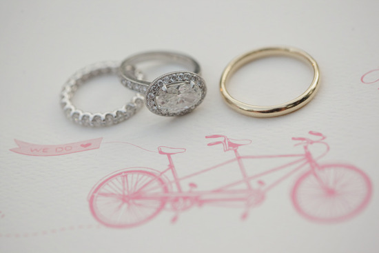 vintage engagement ring with wedding bands atop wedding invitation