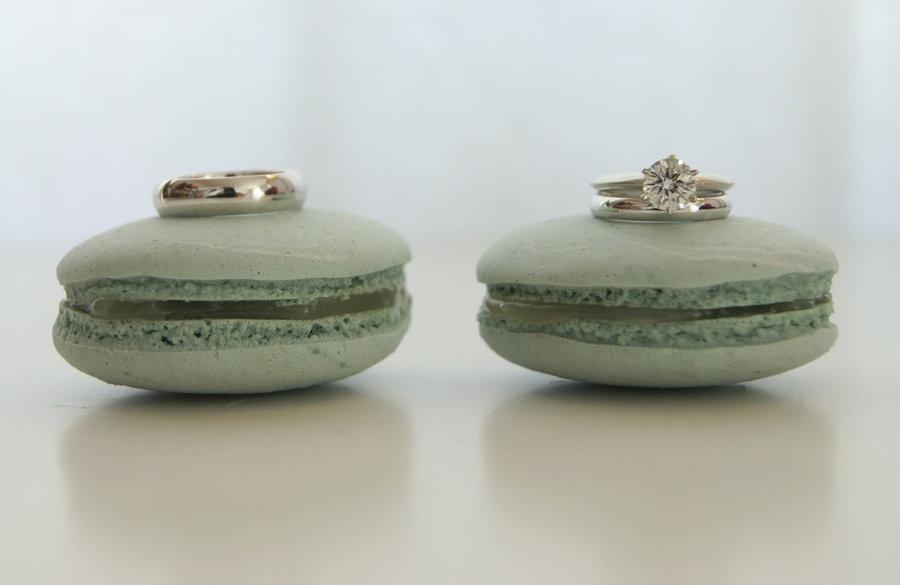 Diamond-engagement-ring-grooms-wedding-band-shot-on-green-macaroons.full