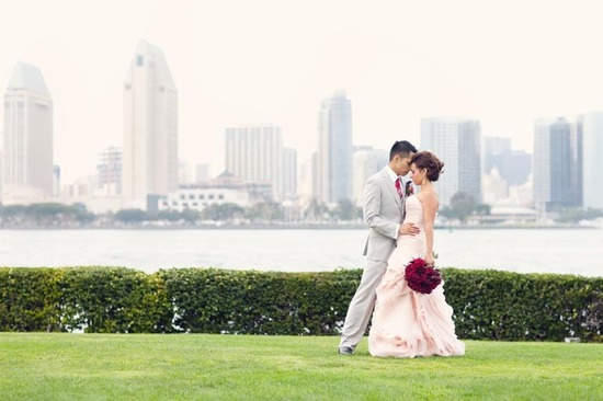 bride wears pink vera wang bridal gown deep red bridal bouquet