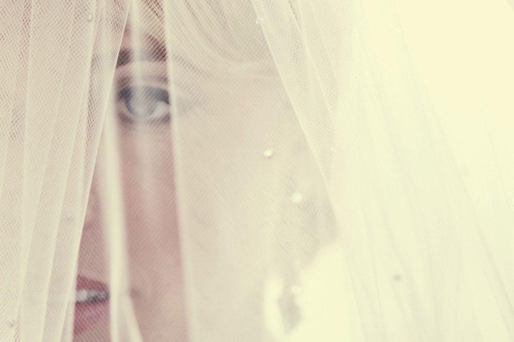 Artistic-wedding-photo-bride-wears-veil-before-ceremony.full