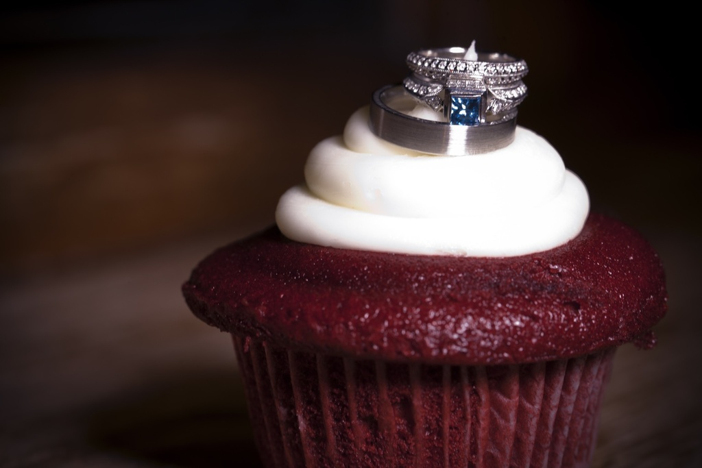 Brides-engagement-ring-wedding-bands-photographed-on-cupcake.full