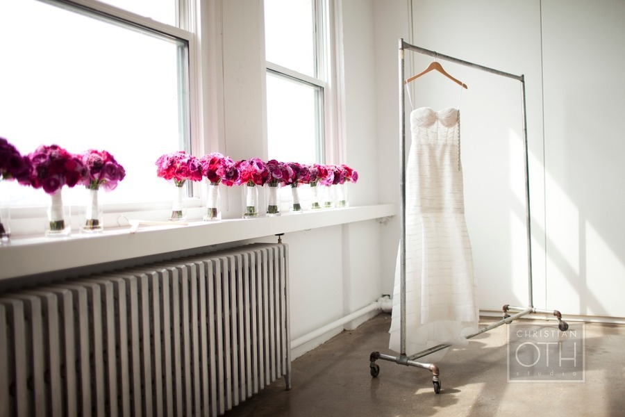 Monique-lhuillier-wedding-dress-hangs-with-pink-wedding-flowers.full