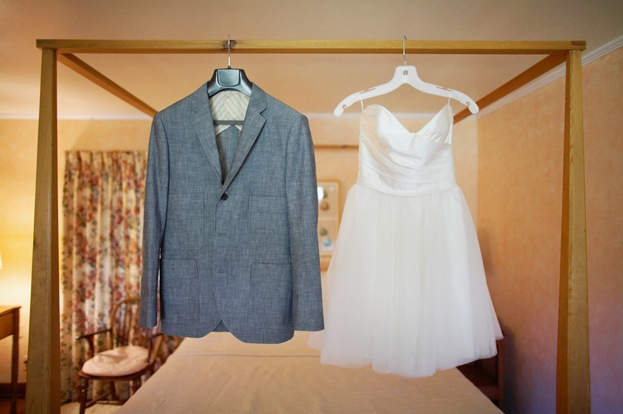 little white dress hangs next to grooms suit coat
