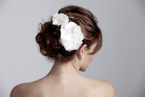 photo of white dual wedding flowers in chic chignon bridal updo