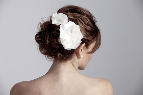 white dual wedding flowers in chic chignon bridal updo