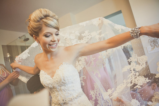 blushing bride wears lace wedding dress sheer bridal veil chic updo