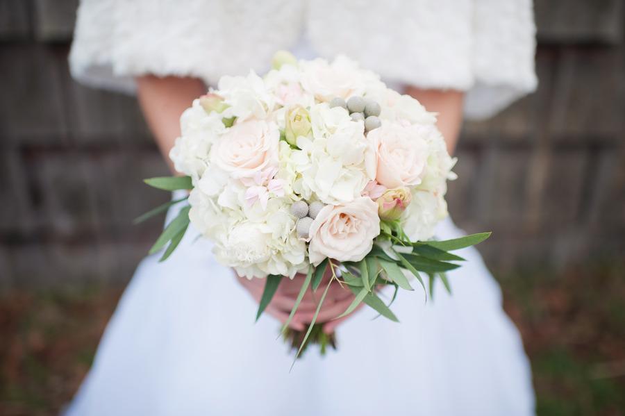 Winter-bride-wears-fur-shrug-holds-ivory-light-pink-bridal-bouquet.full
