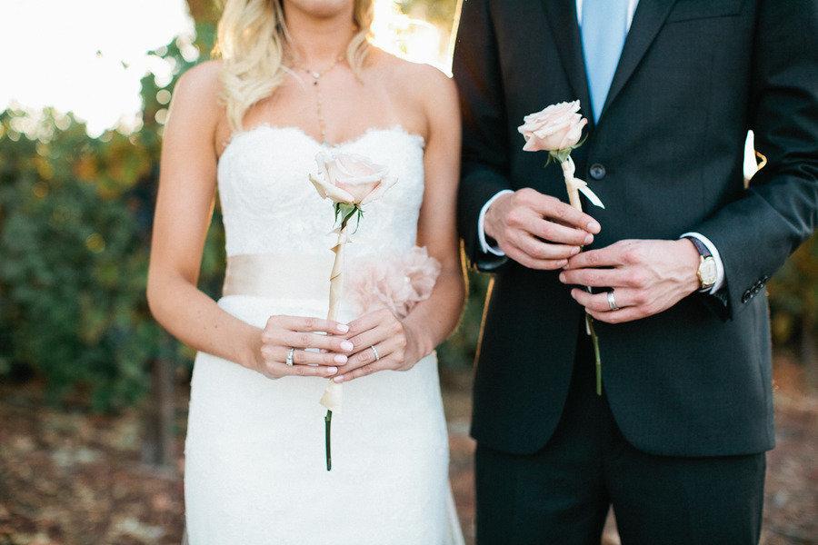 Romantic-wedding-photography-bride-groom-hold-single-rose.full