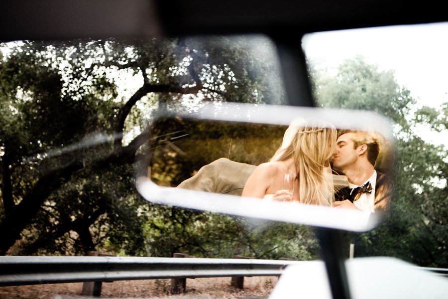 Boho-bride-black-tie-groom-kiss-in-vintage-wedding-car.full