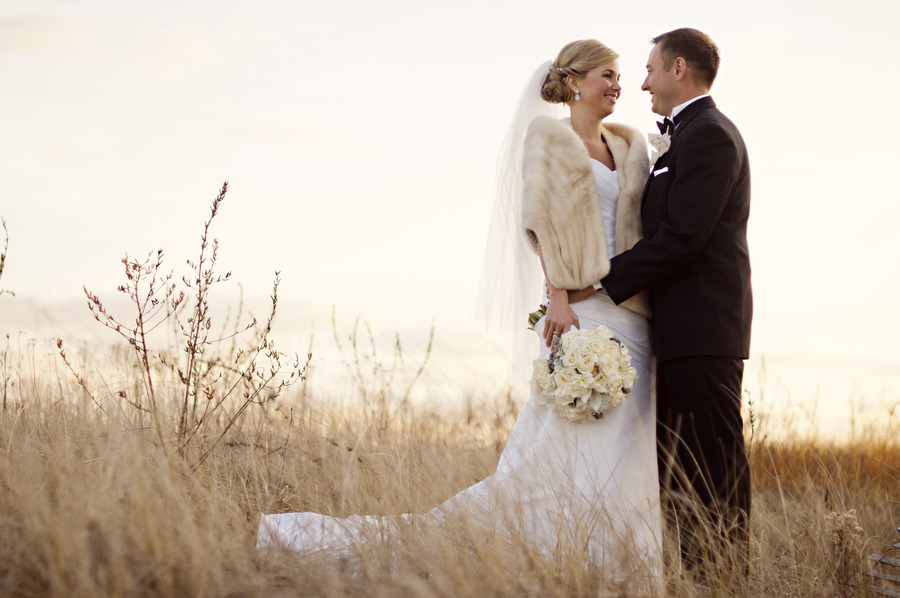 fall bride and groom pose outside fur shrug ivory bridal bouquet