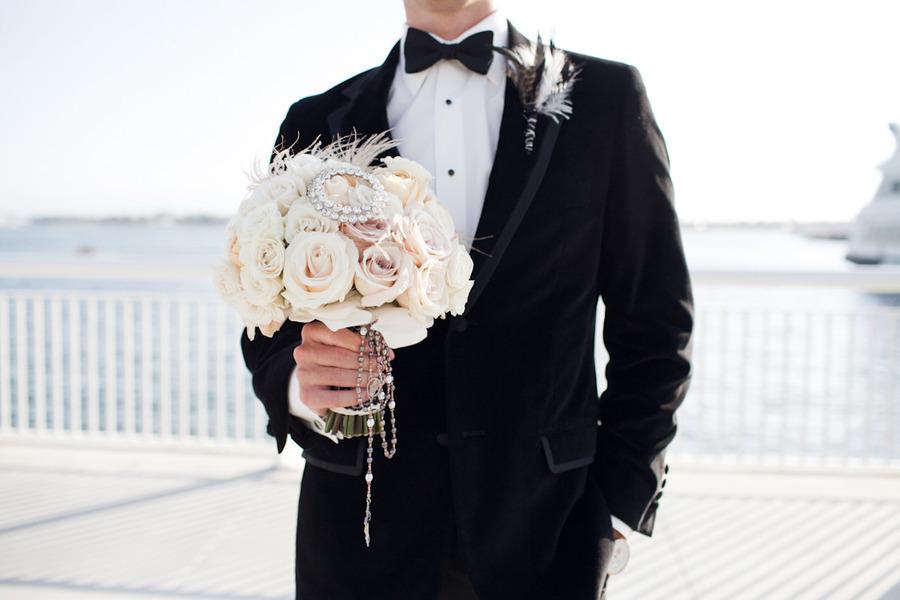 Black-tie-groom-holds-brides-elegant-bridal-bouquet.full