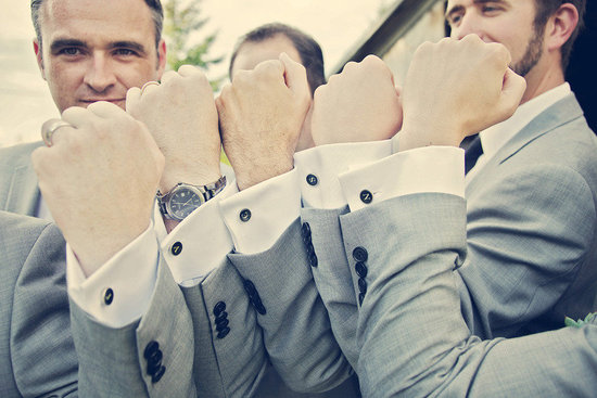 groom with groomsmen show off cufflinks