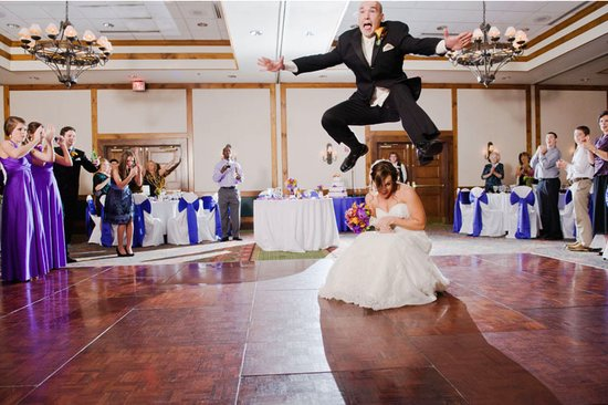 memorable wedding photos day of photography groom jumps bride during first dance