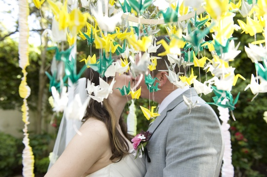 whimsical garden wedding green yellow paper cranes outdoor kiss