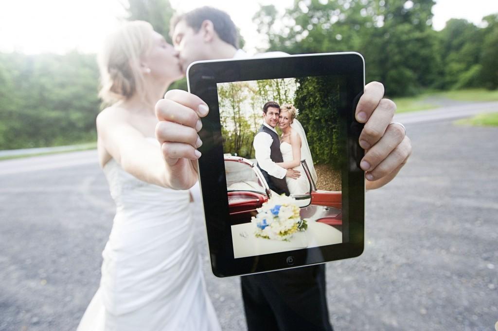 Bride-groom-kiss-with-wedding-photo-on-ipad.full