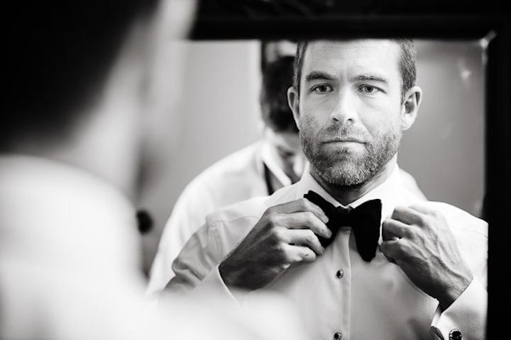 Black-tie-groom-gets-ready-in-mirror.full