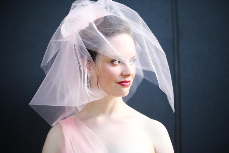 Bride-wears-blush-pink-wedding-dress-birdcage-veil.full