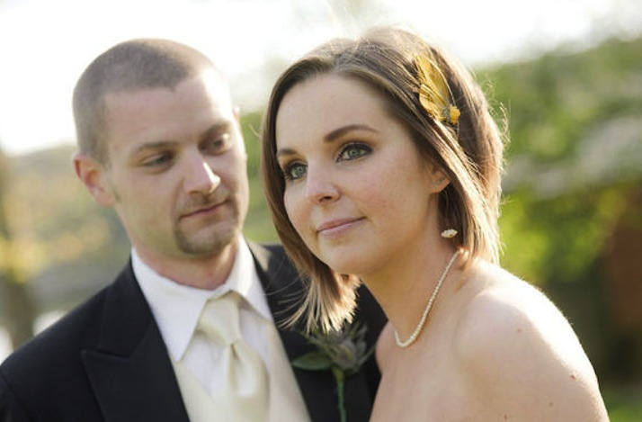 bride with short hair poses outside wedding venue with groom