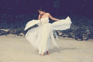 photo of Bohemian Bride on a Beach Draped in Lace